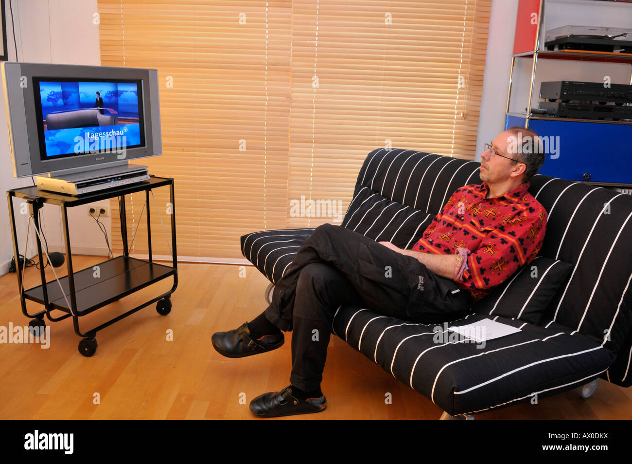 Man Sitting On Couch Watching TV Stock Photo: 16688125 - Alamy