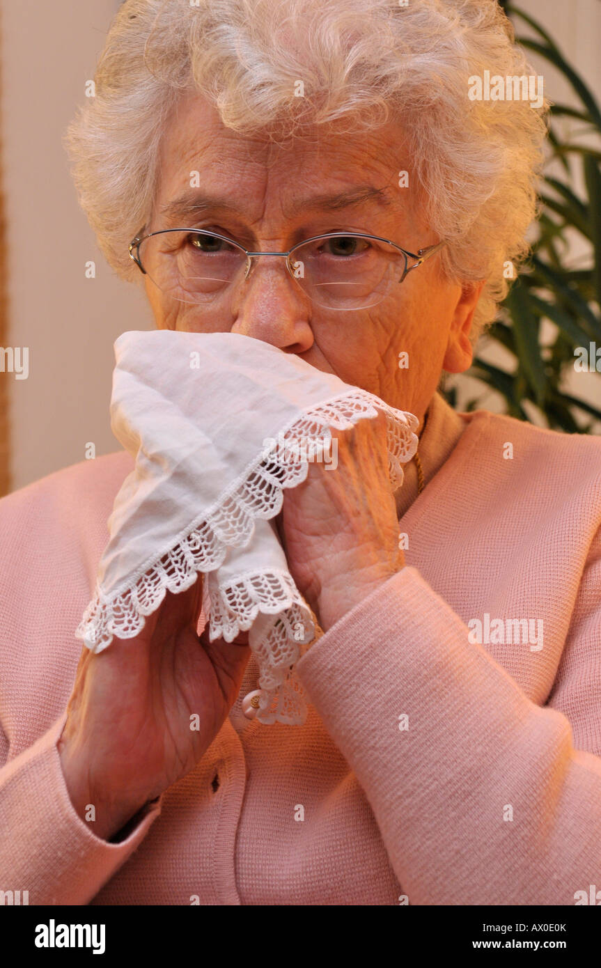 Elderly woman bowing her nose with a cloth handkerchief Stock Photo