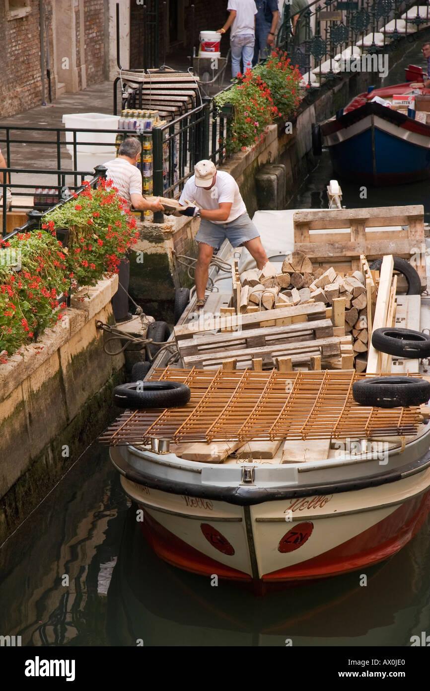 Boat with load of firewood on Rio di Santa Maria Zobenigo San Marco Sestiere Venice Italy - Stock Image
