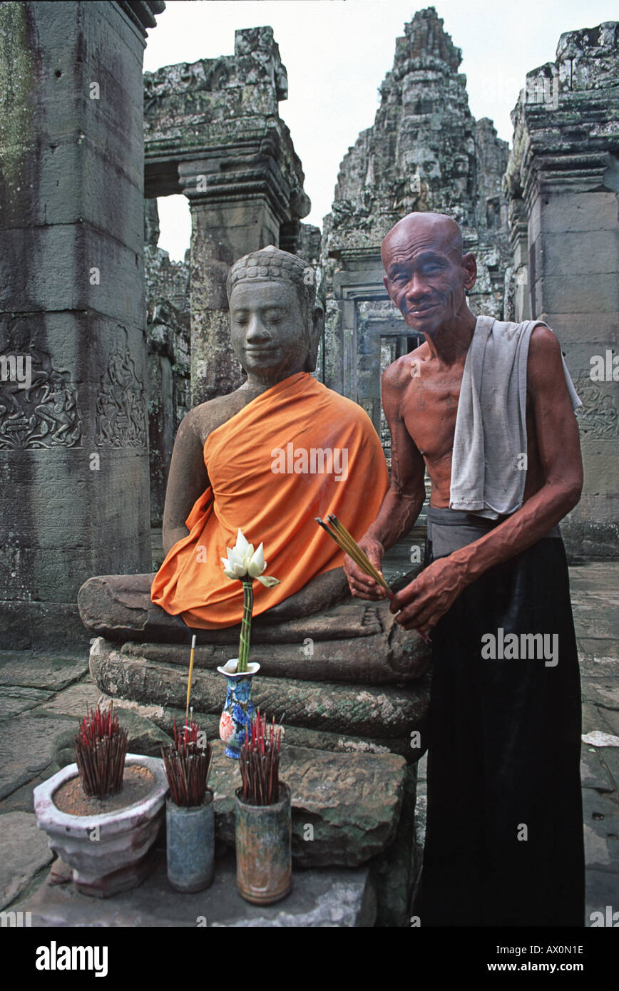 Portrait of a friendly monk tending to a shrine with a saffron robed Buddha image at the Bayon Angkor Thom Cambodia - Stock Image