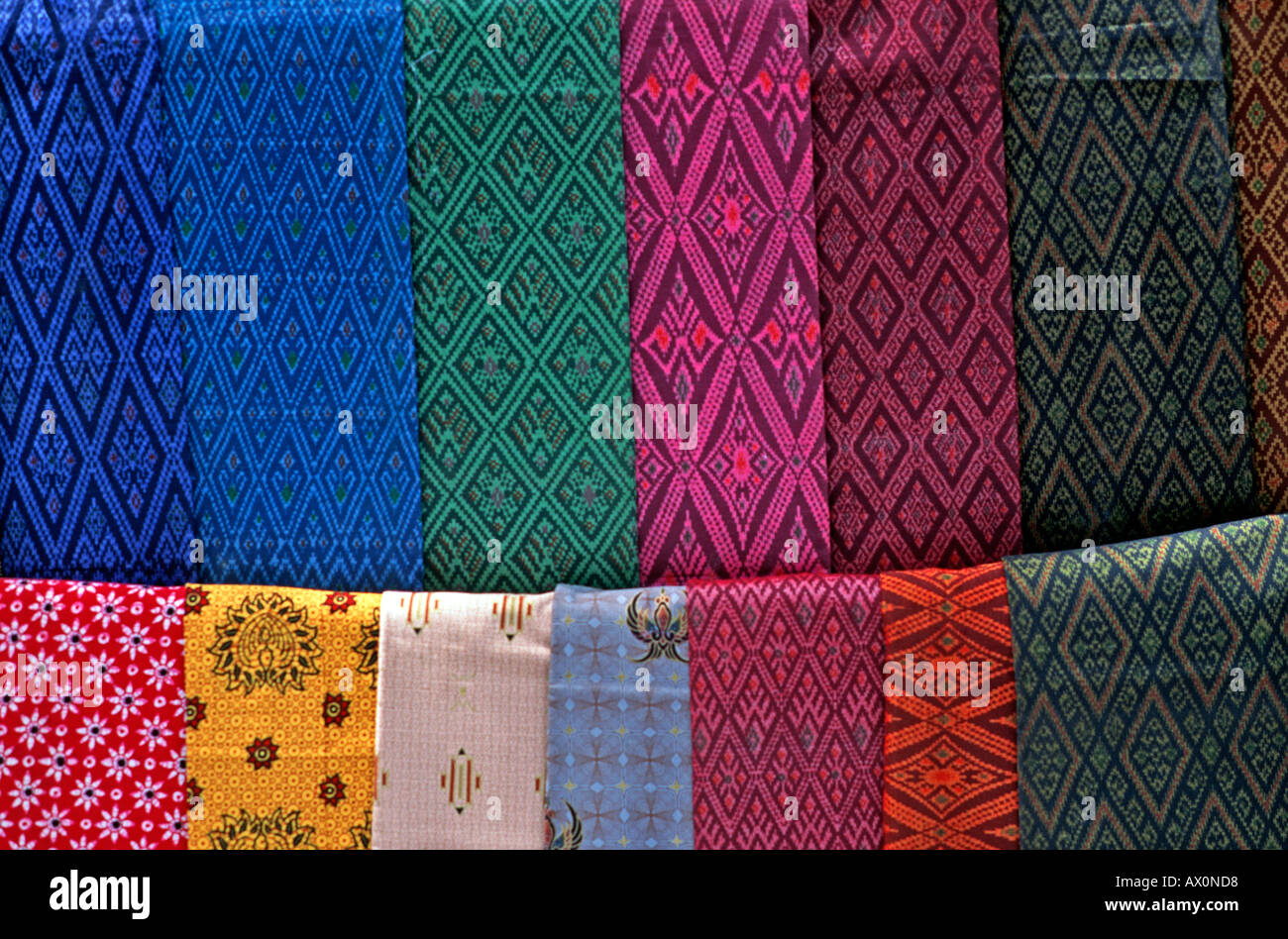 A selection of hand woven ikat patterned fabrics for sale on a stall Angkor town Siem Reap Cambodia - Stock Image