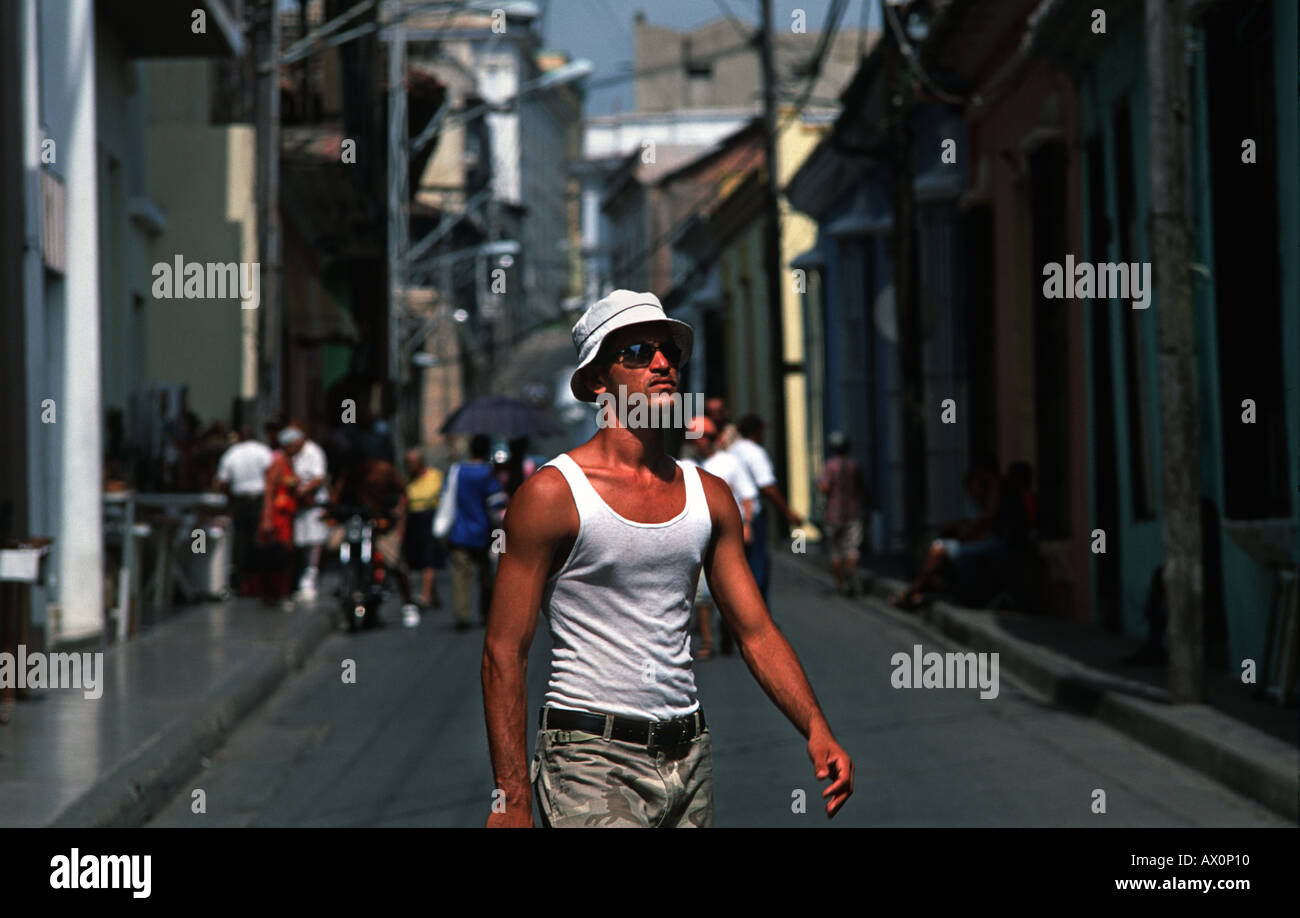 Portrait of a young and trendy Cuban man in cap and shades walking in the street Santiago de Cuba CUBA - Stock Image