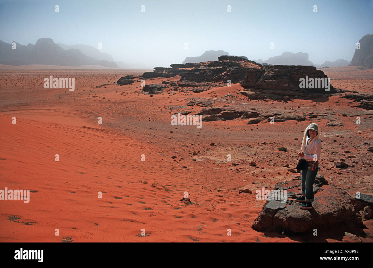 Red sand floor of the desert with rocky outcrops called Jebels in the distance Wadi Rum Jordan - Stock Image