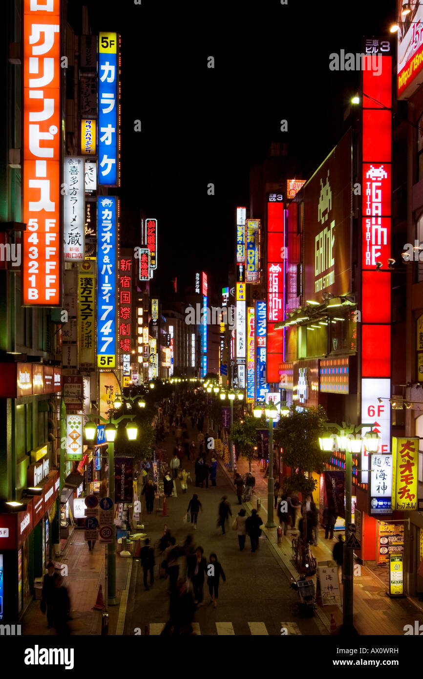 Busy scene at night with many bright glowing signs and people walking in street in Shinjuku Tokyo Japan - Stock Image