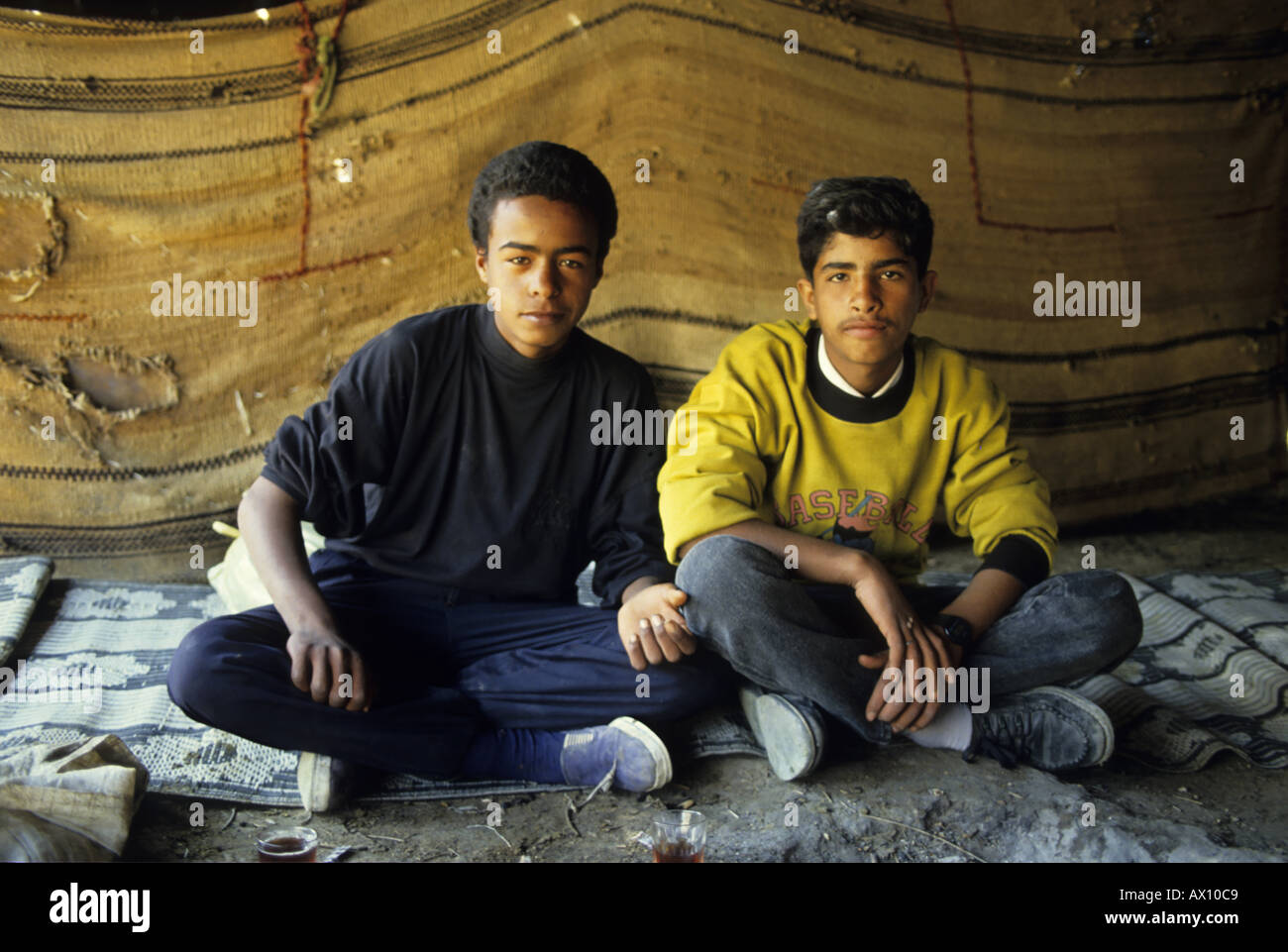 Portrait Of Two Young Bedouins Having A Tea Under Their Tents In The Desert Stock Photo