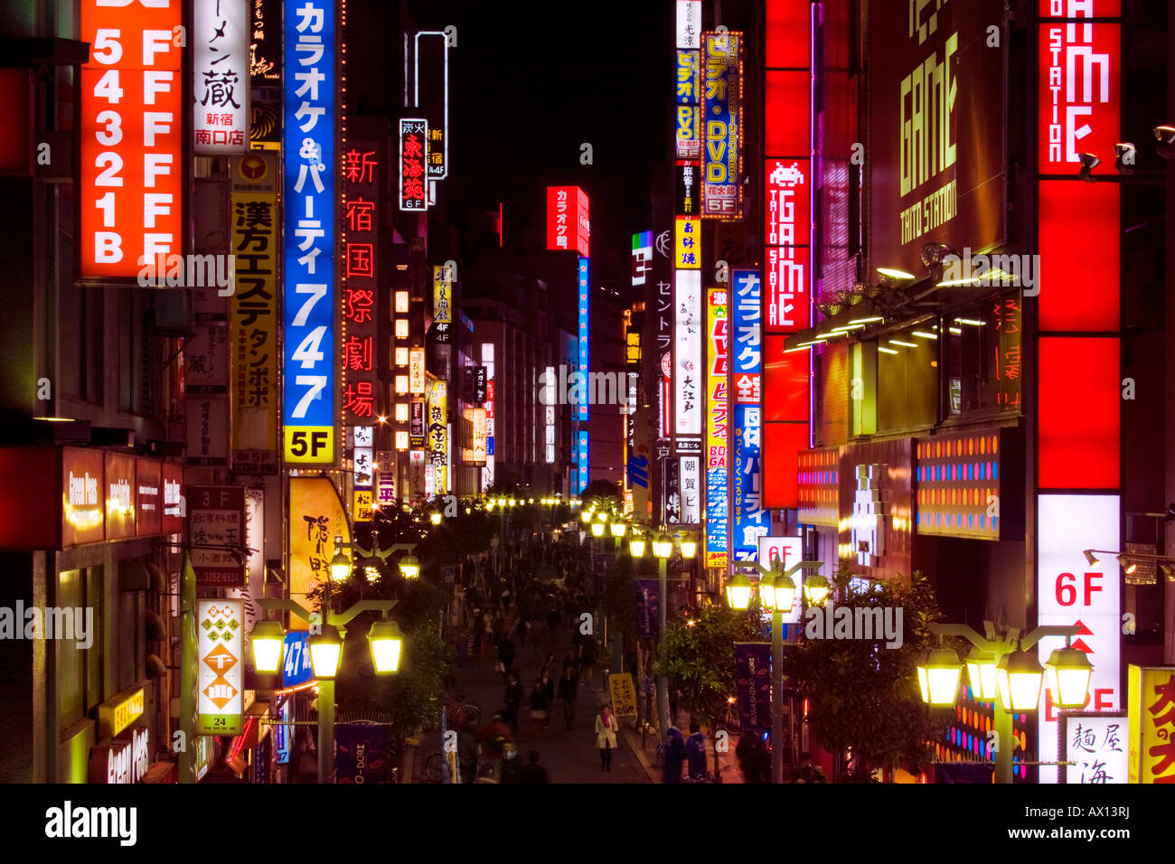Busy scene at night with many bright glowing signs and people walking in street in Shinjuku, Tokyo, Japan. - Stock Image