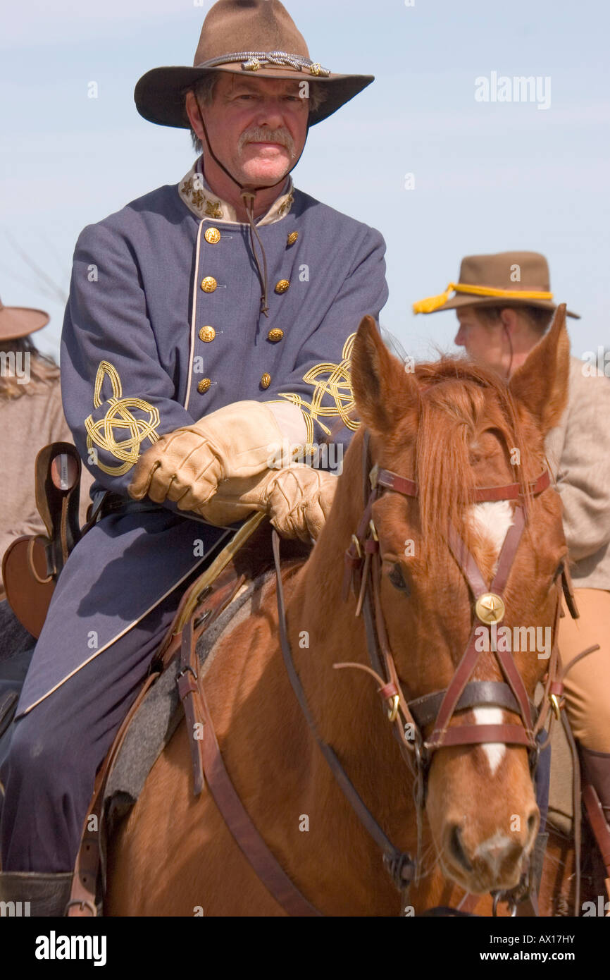An American Civil War reenactor, representing the Confederate Army, sits astride his horse waiting for a mock battle - Stock Image