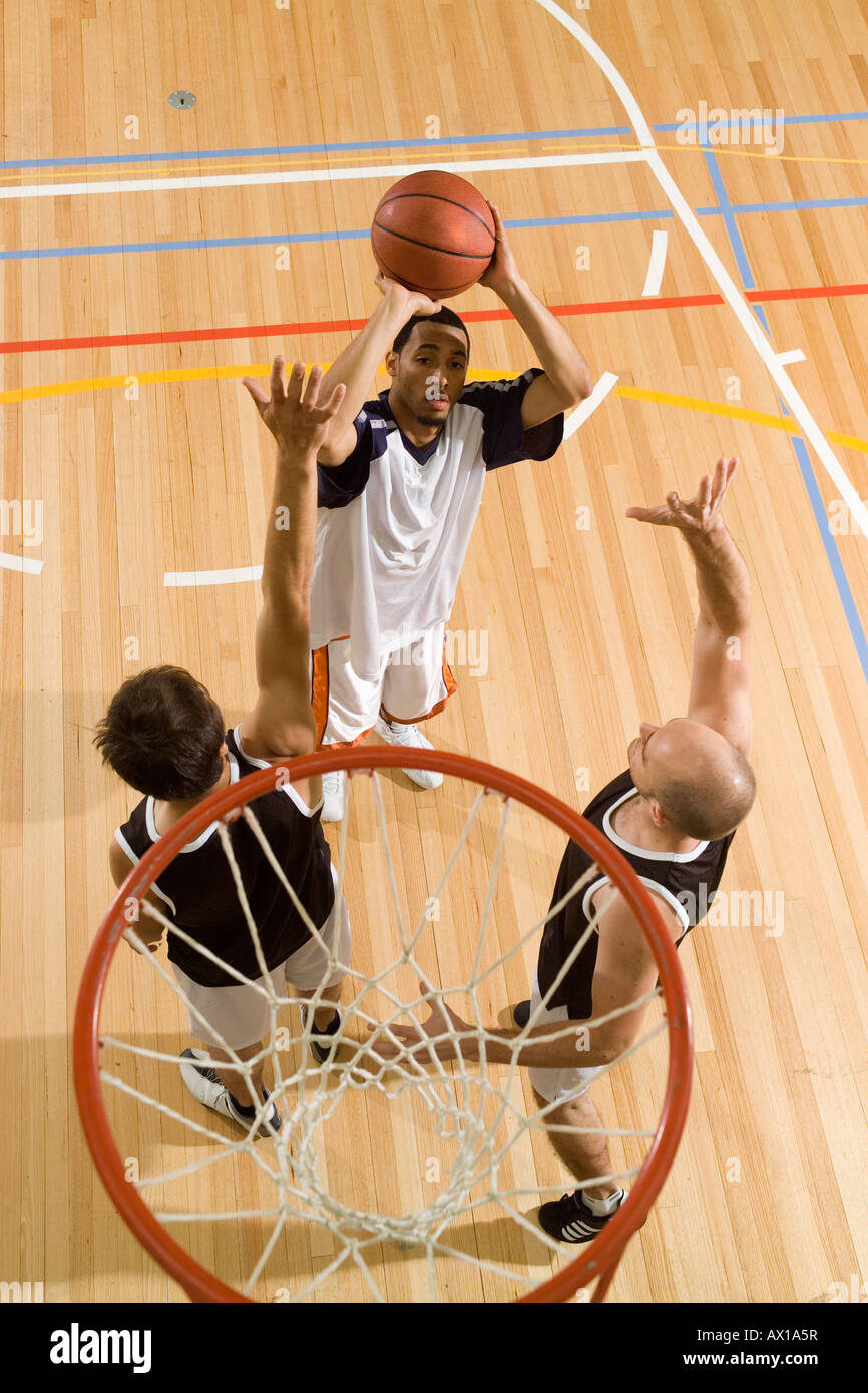 Three young men playing basketball - Stock Image