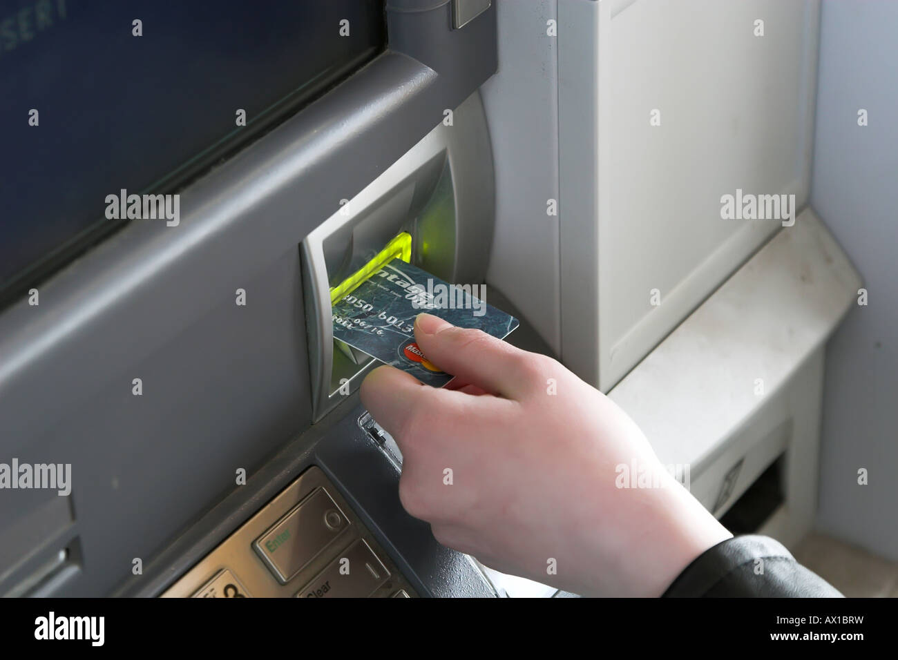 A woman inserting her debit card into an ATM - Stock Image
