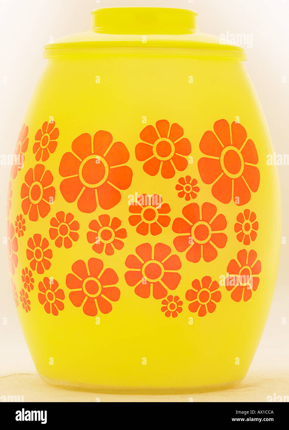 Yellow glass jar with painted orange flowers L3 - Stock Image