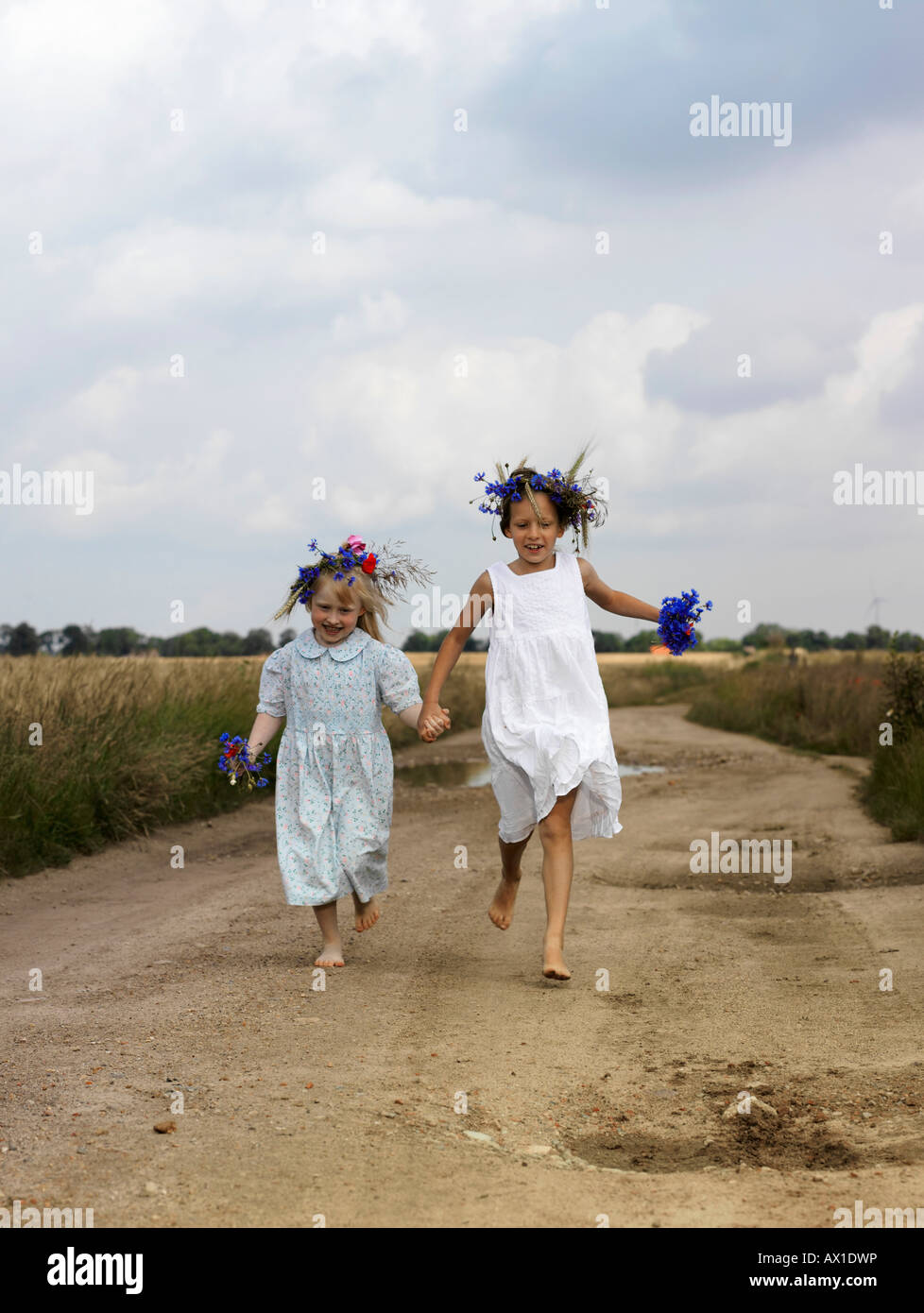 Two young girls running along a country road - Stock Image