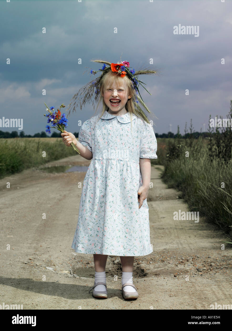 A girl standing on a country road and holding wildflowers - Stock Image