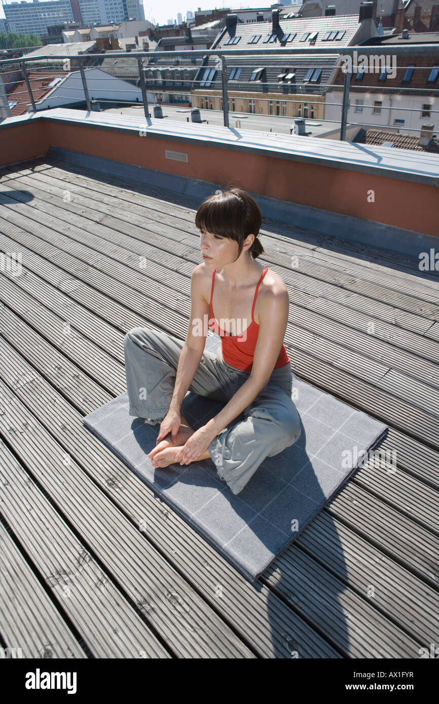 A woman stretching on a rooftop terrace - Stock Image