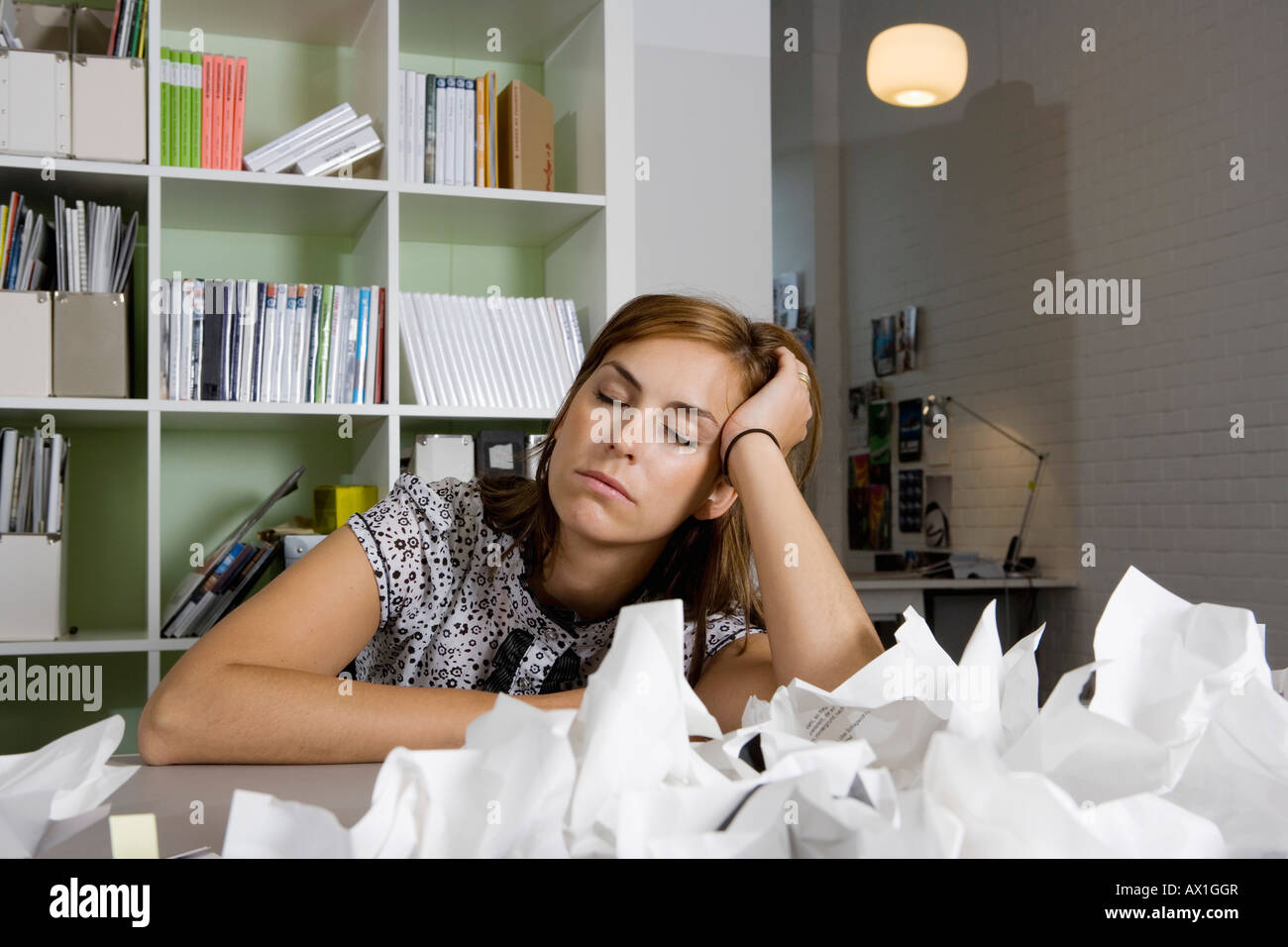 A woman sitting at a desk behind a pile of screwed up paper - Stock Image