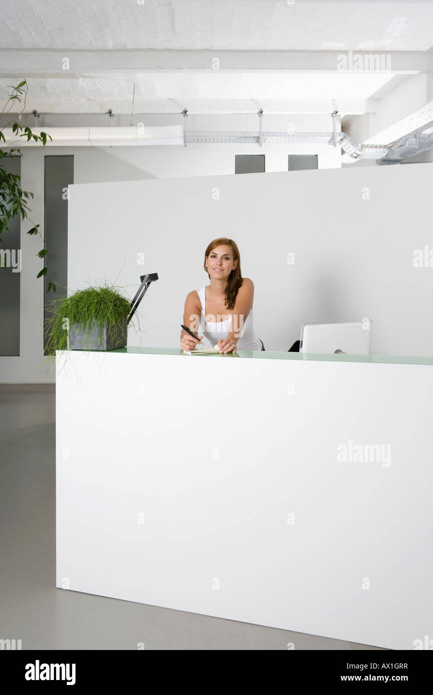 office reception desk. A Woman Behind An Office Reception Desk With Notepad And Pen