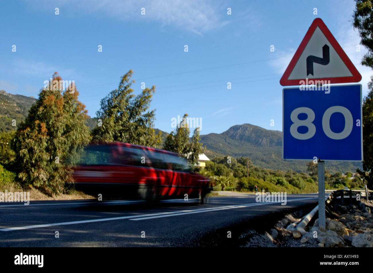 Speeding car on a highway with speed limit road signs at 80 km per hour and warning of bends in the road, Spain - Stock Image