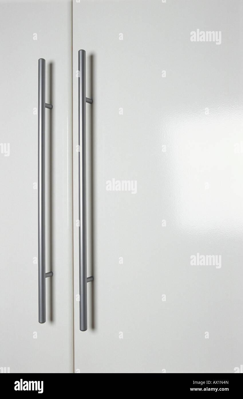 Pair of chrome guardsman door handles on white cupboard doors Stock ...