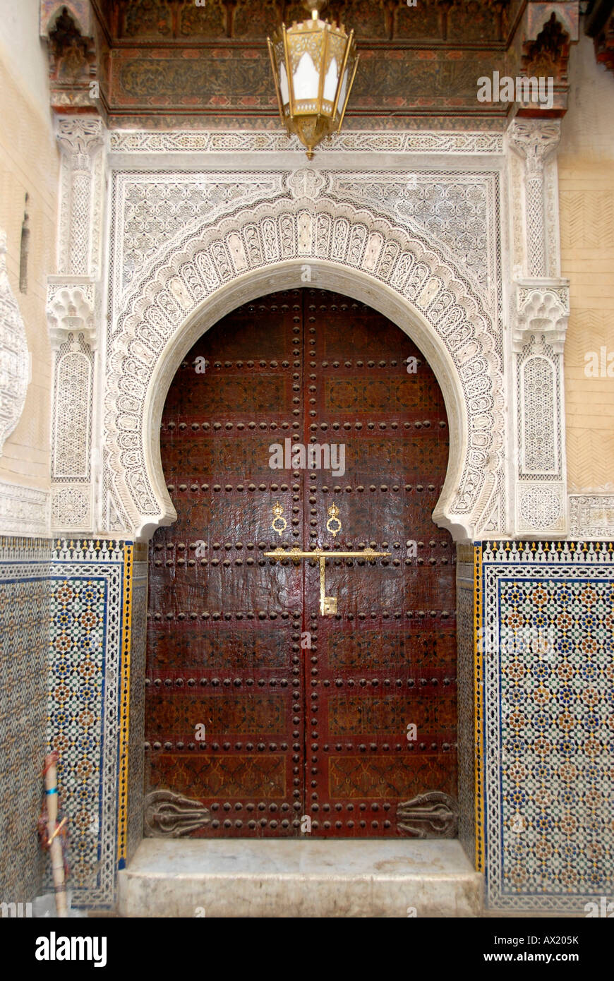 Richly decorated wooden entrance gate medina Fes El Bali Morocco - Stock Image