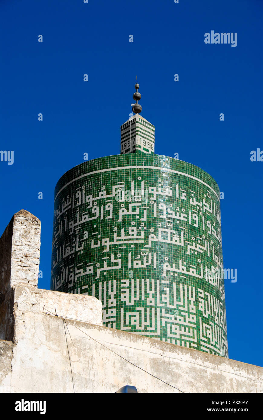 Green round minaret decorated with Arabic script islamic place of pilgrimage Moulay-Idriss Morocco - Stock Image