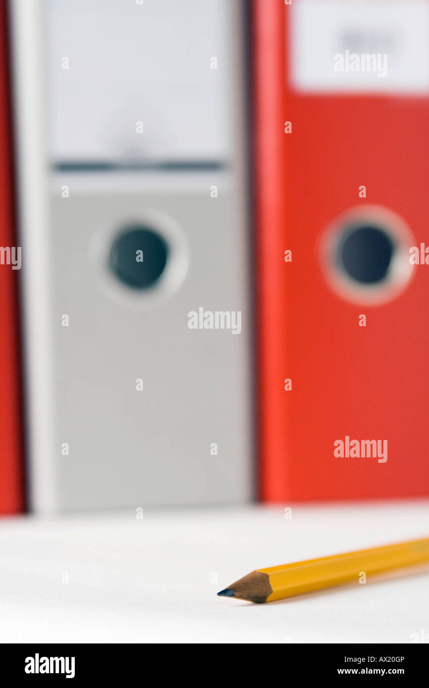 Orange and grey binders and a pencil - Stock Image