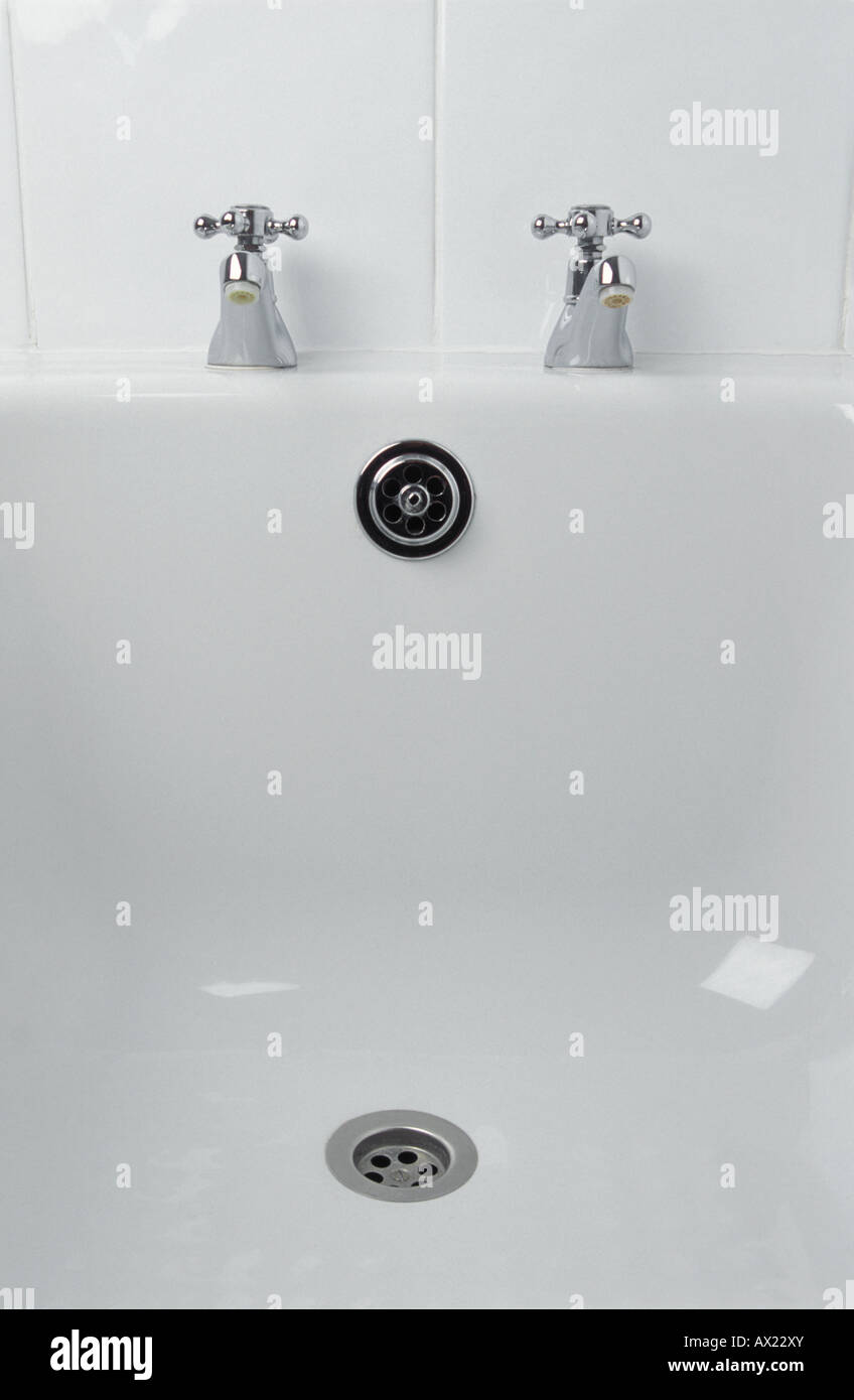 Traditional chrome taps on white acrylic bath - Stock Image