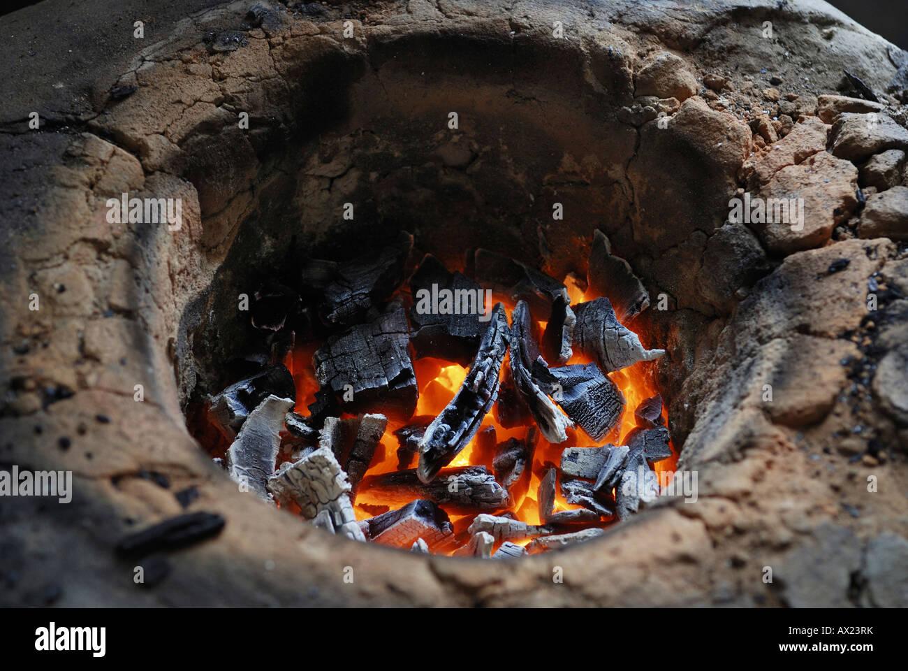 Simple earthen stove with glowing charcoal, Amazon Basin, Brazil - Stock Image