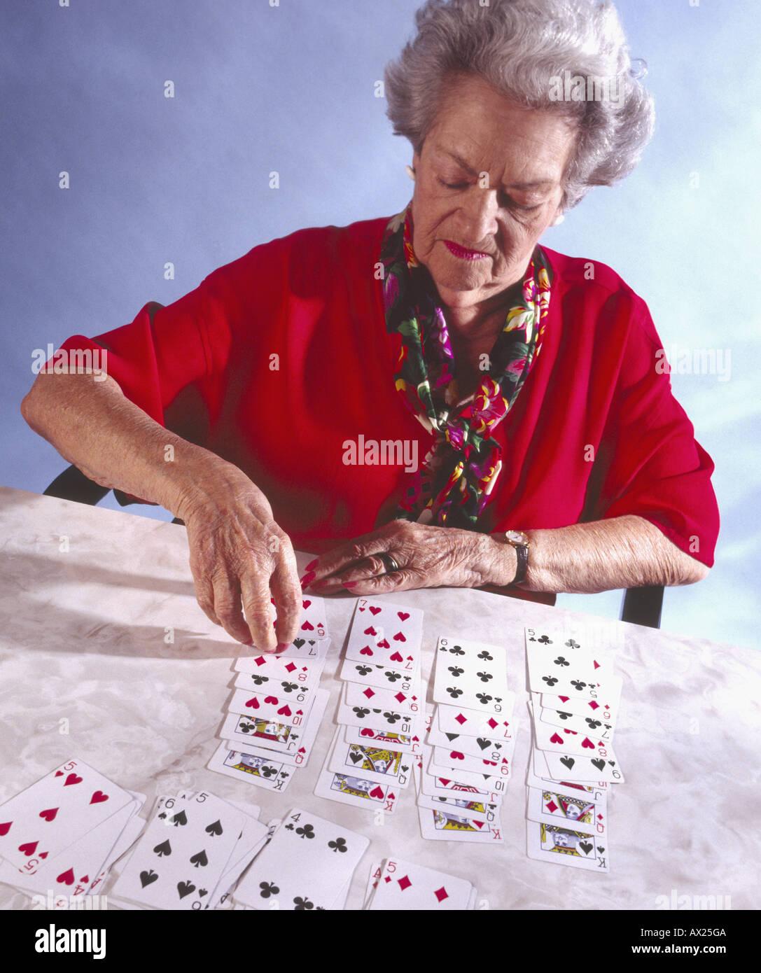 elderly woman playing solitaire - Stock Image