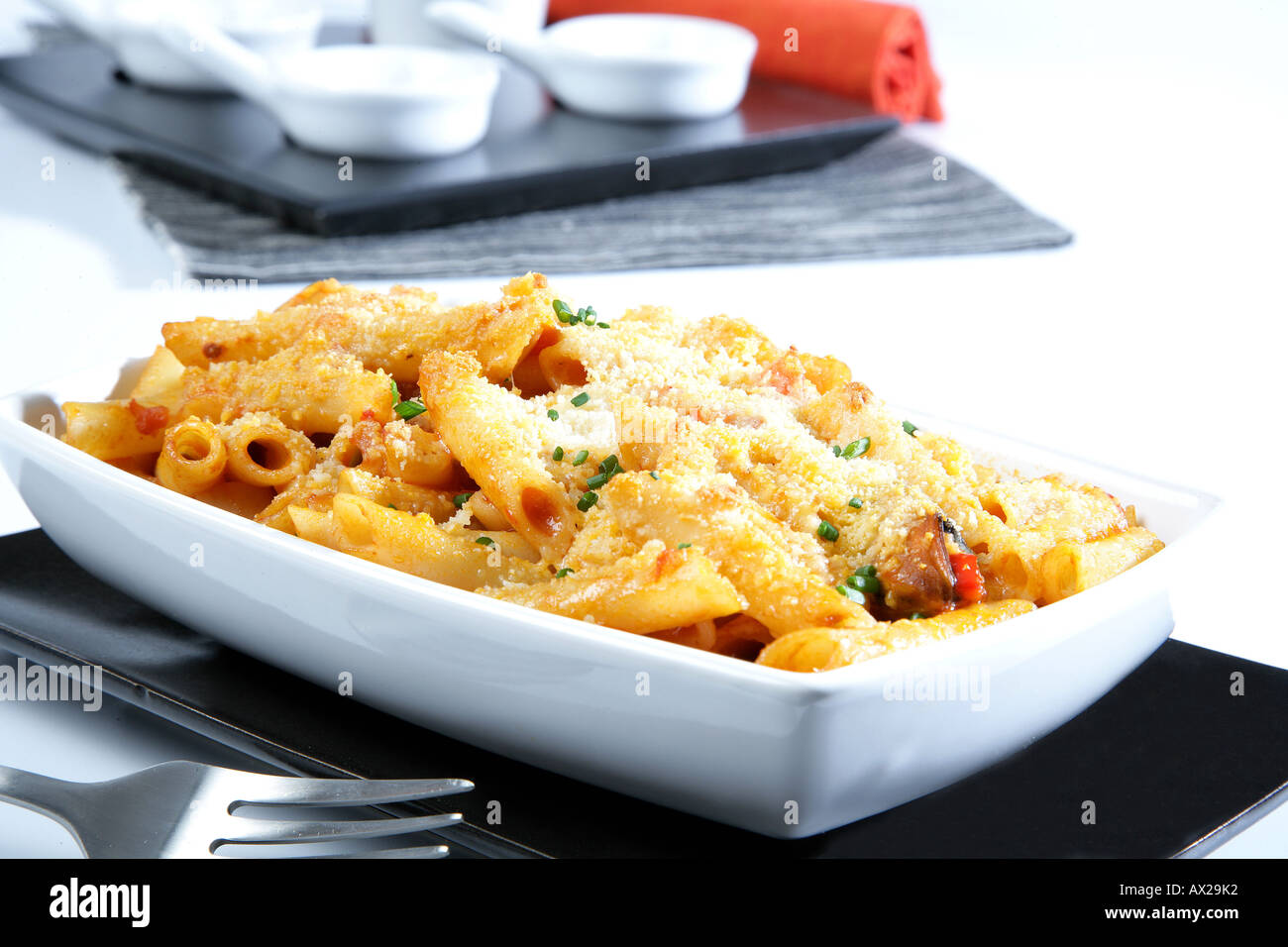 Penne au gratin with fish seafood and grated cheese - Stock Image
