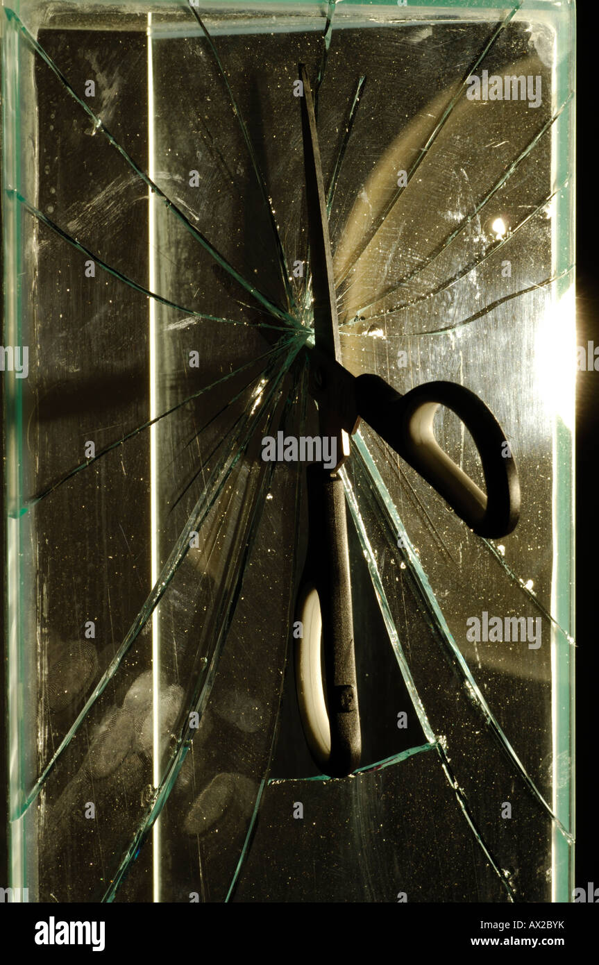 a pair of scissors cutting through a sheet pane of glass with cracking and shards splinters sharp wrong tool for - Stock Image