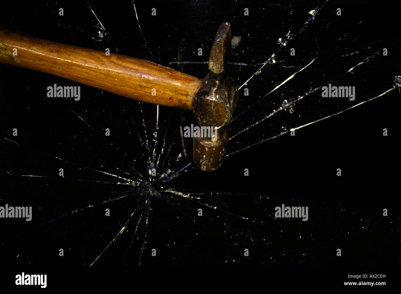 a hammer smashing through a pane of glass or window shattering the glass - Stock Image