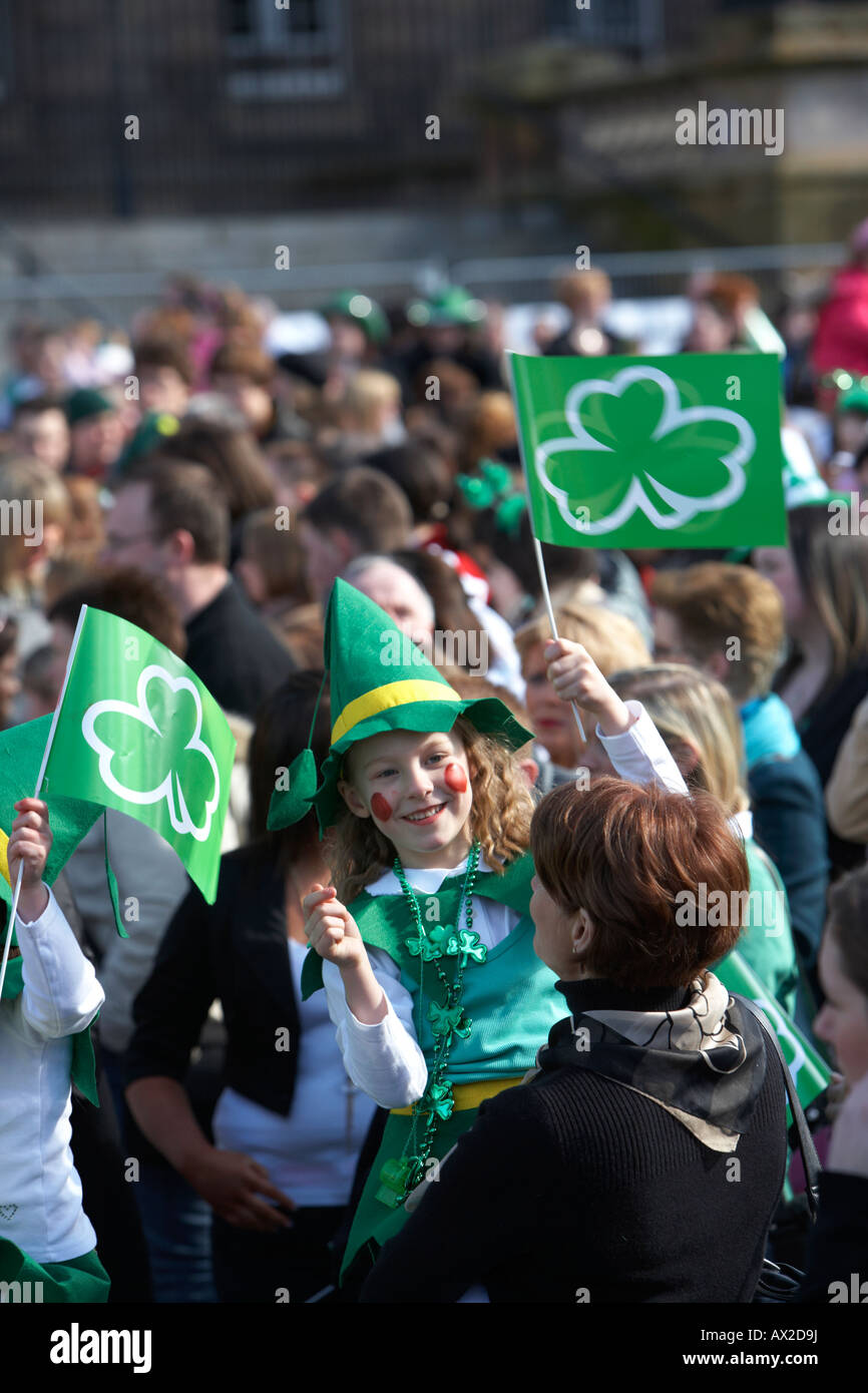 young girl in fancy dress irish costume waving flag in the crowd at the concert and carnival in custom house square Stock Photo