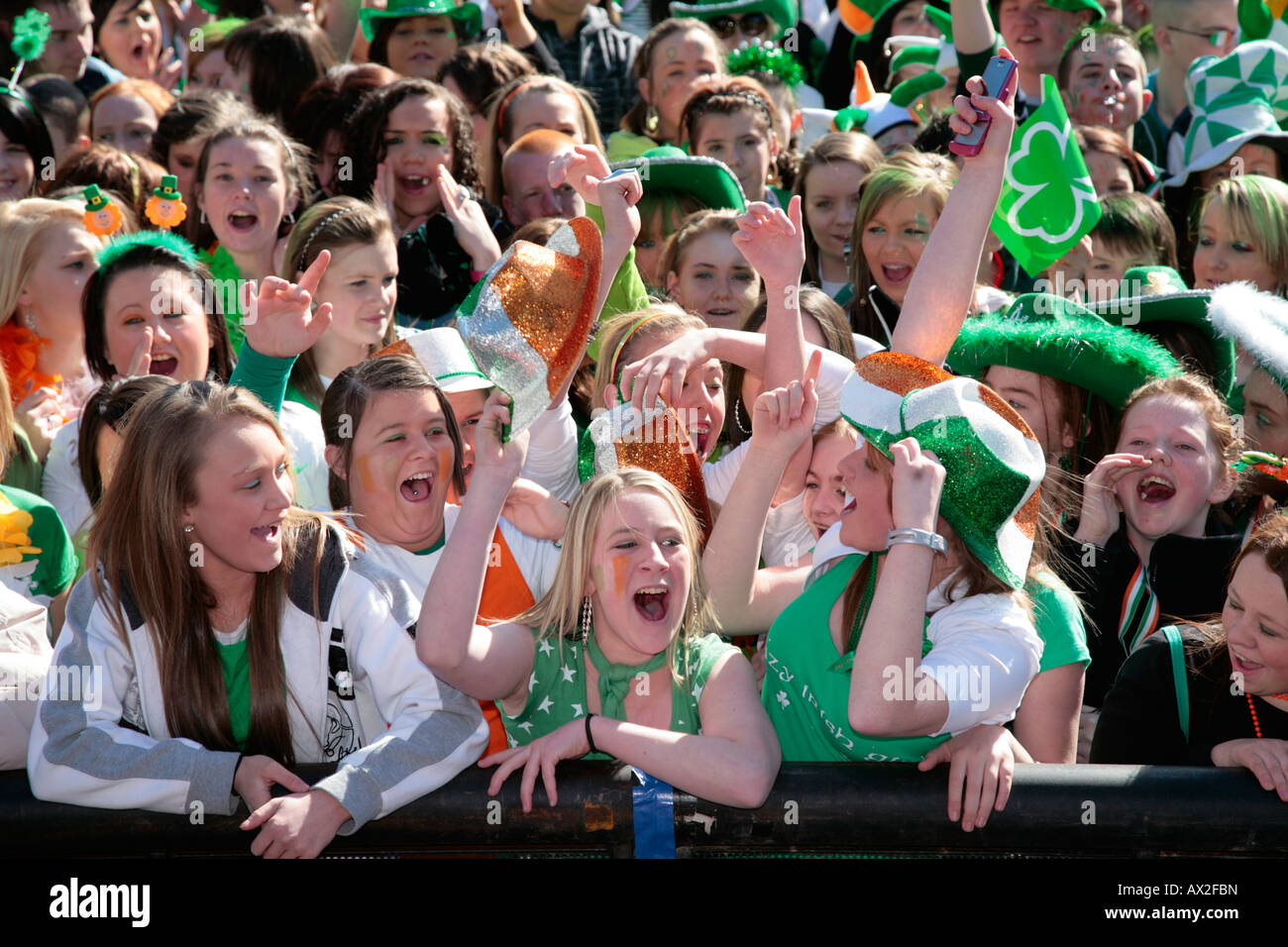 young teenage irish girls at the front of the crowd at the st patricks day concert and carnival in custom house - Stock Image