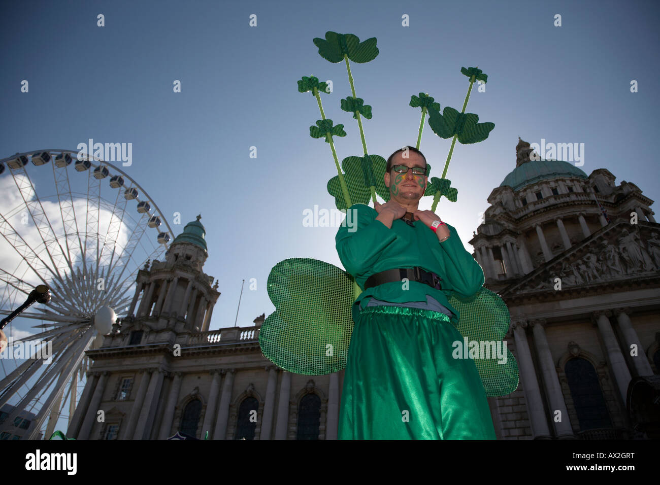 stiltwalker dressed in green wearing shamrocks at belfast city hall and big wheel before the parade and carnival - Stock Image