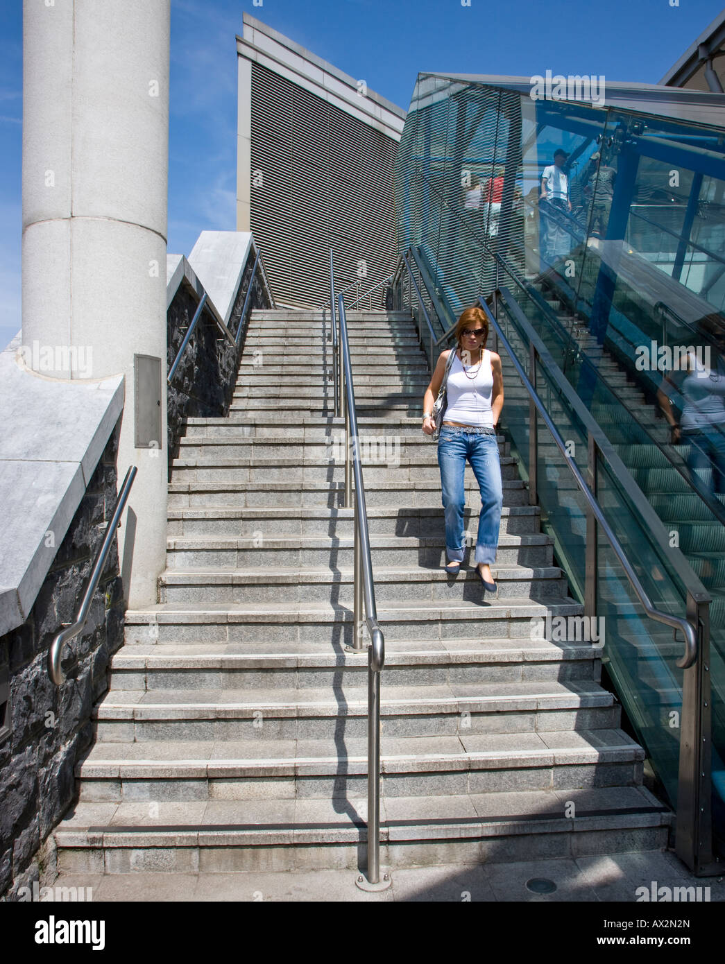 young woman descending steps - Stock Image
