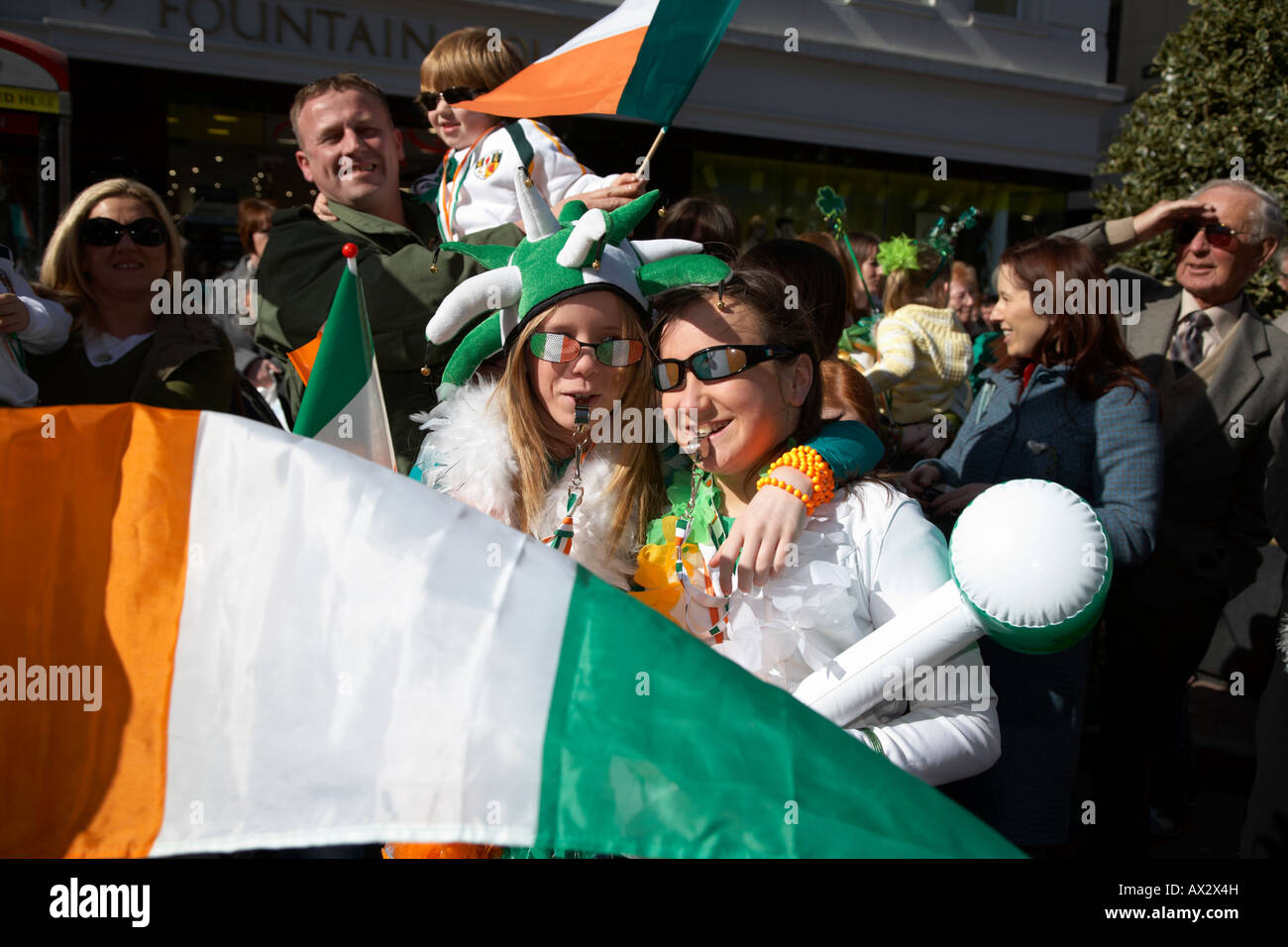 two young girls with irish flag standing waiting on the parade and carnival on st patricks day belfast northern - Stock Image