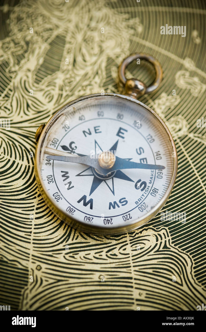 Vintage compass resting on a world map - Stock Image