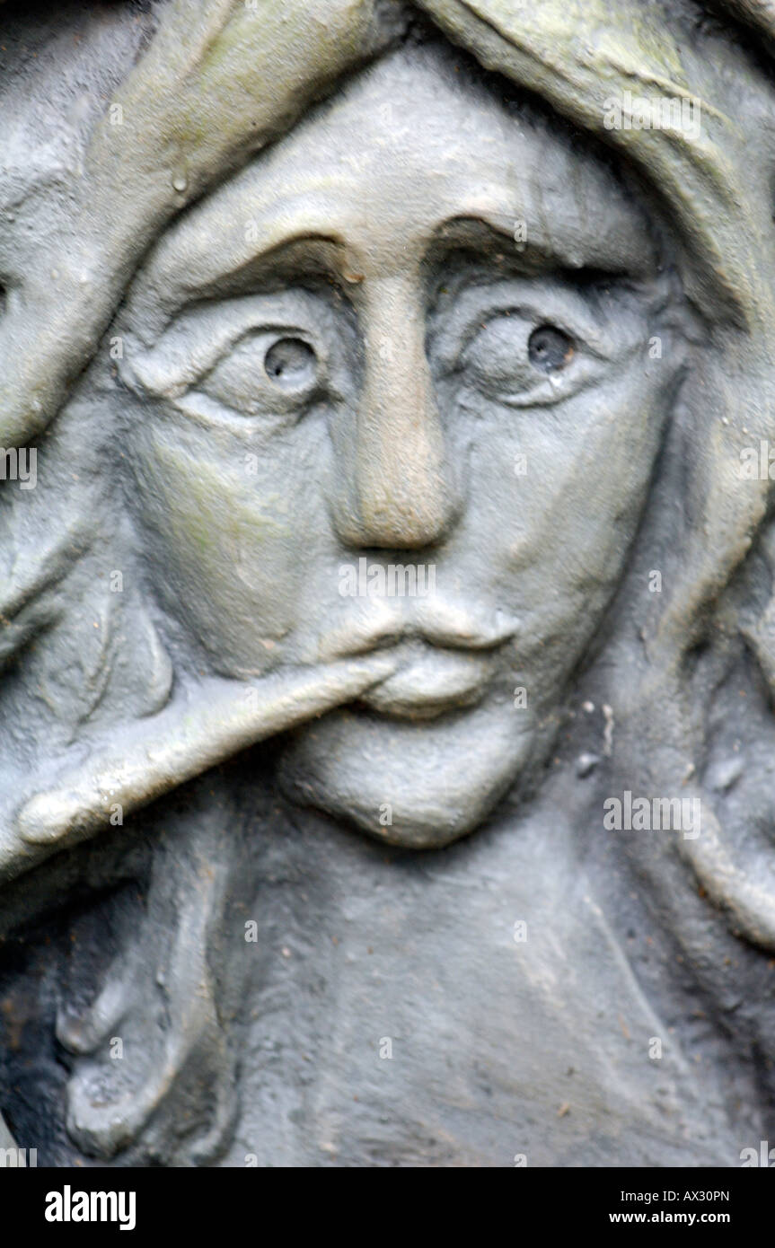 a stone garden statue sculpture piece of statuary finger in mouth giving impression facial expressions of being - Stock Image