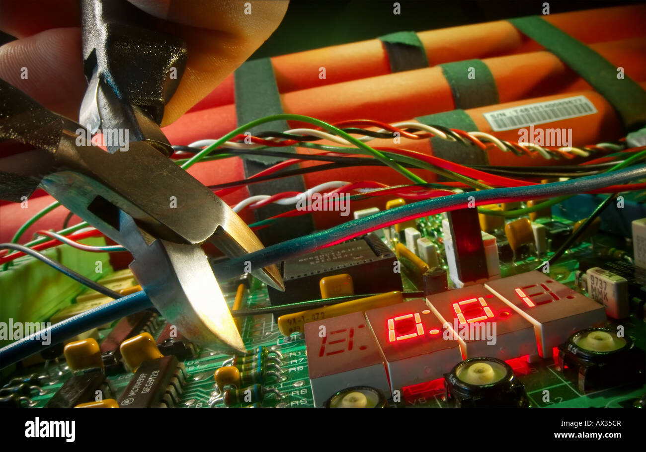 Time bomb displaying numbers 0:01 and hand about to cut blue wire Stock Photo