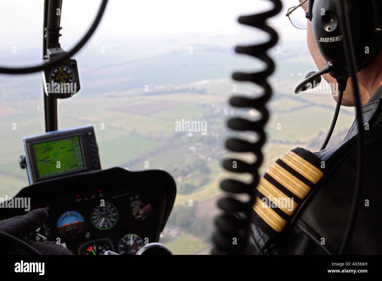 Helicopter pilot flying over countryside in Wiltshire, UK - Stock Image