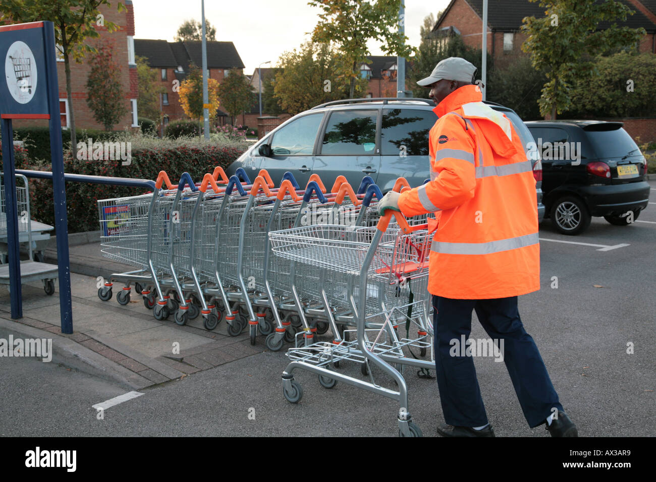trolley collector in car park - Stock Image