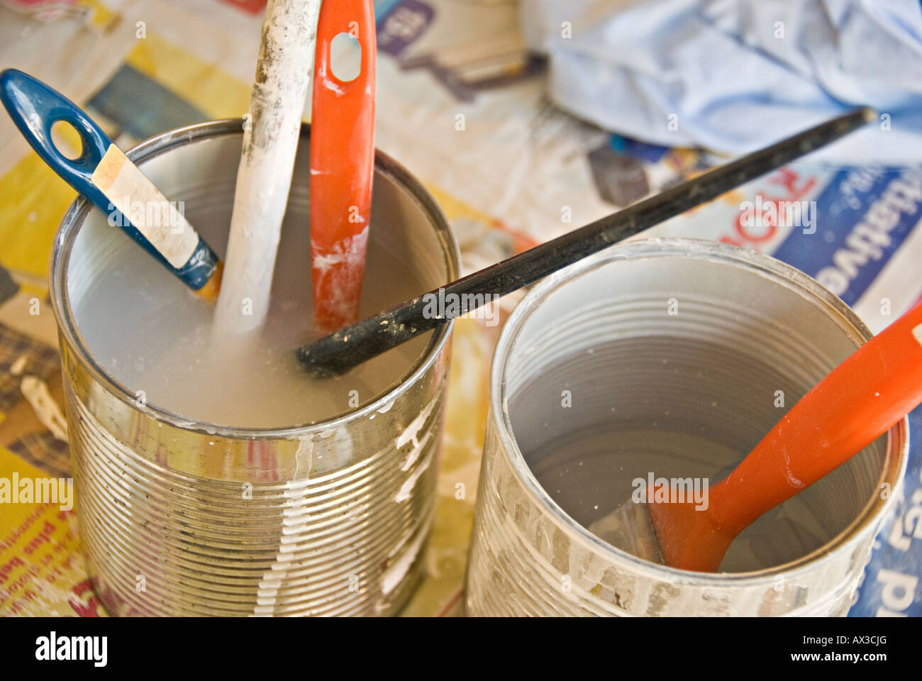 Paintbrushes soak in  water cans - Stock Image