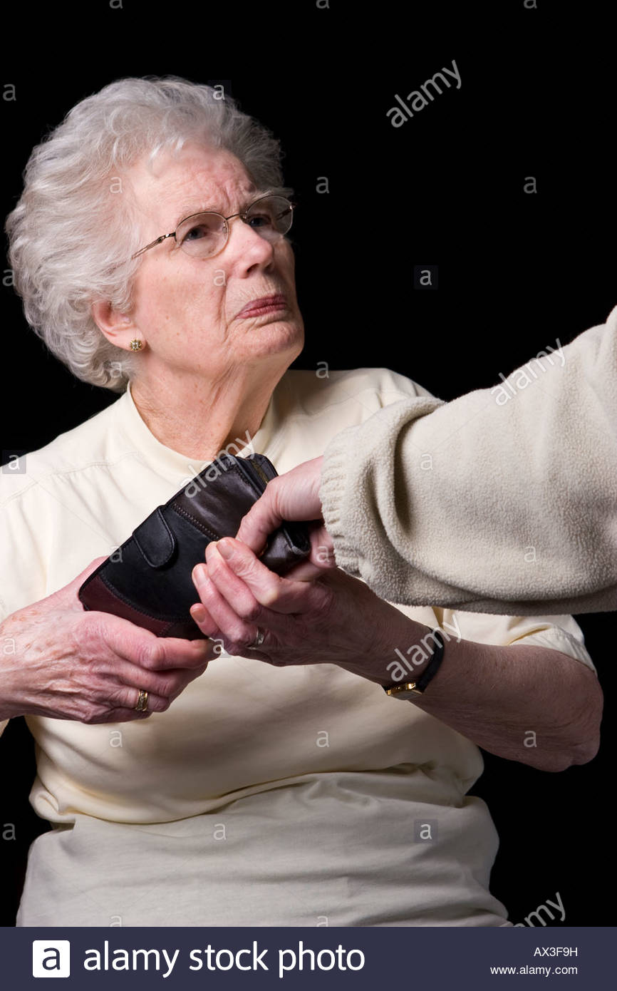 A purse being snatched from an old woman. - Stock Image