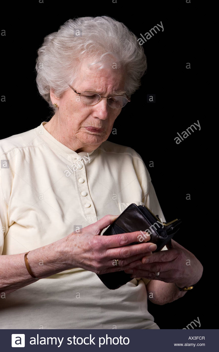 An old woman looking in her purse. - Stock Image