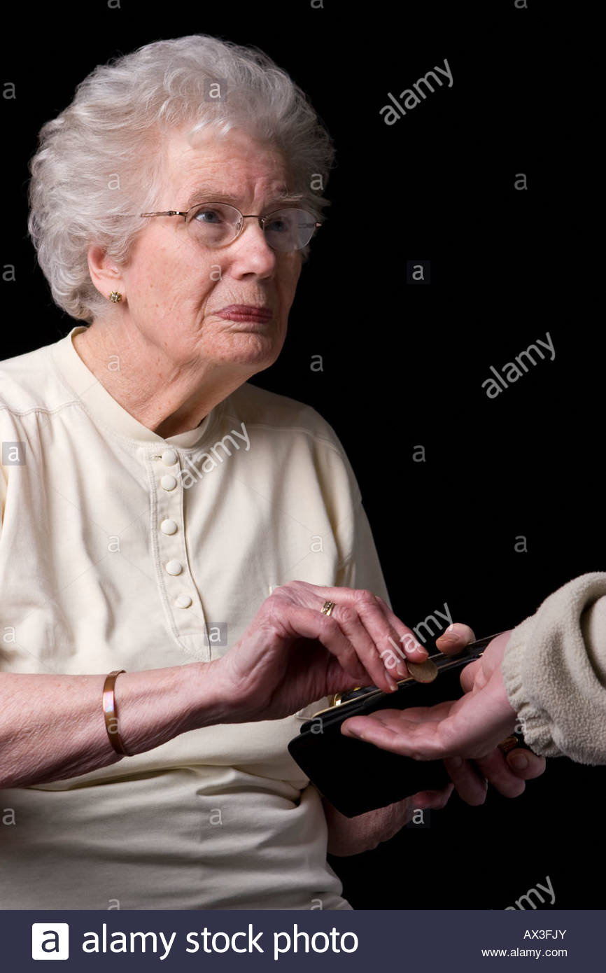 An old woman paying handing money. - Stock Image