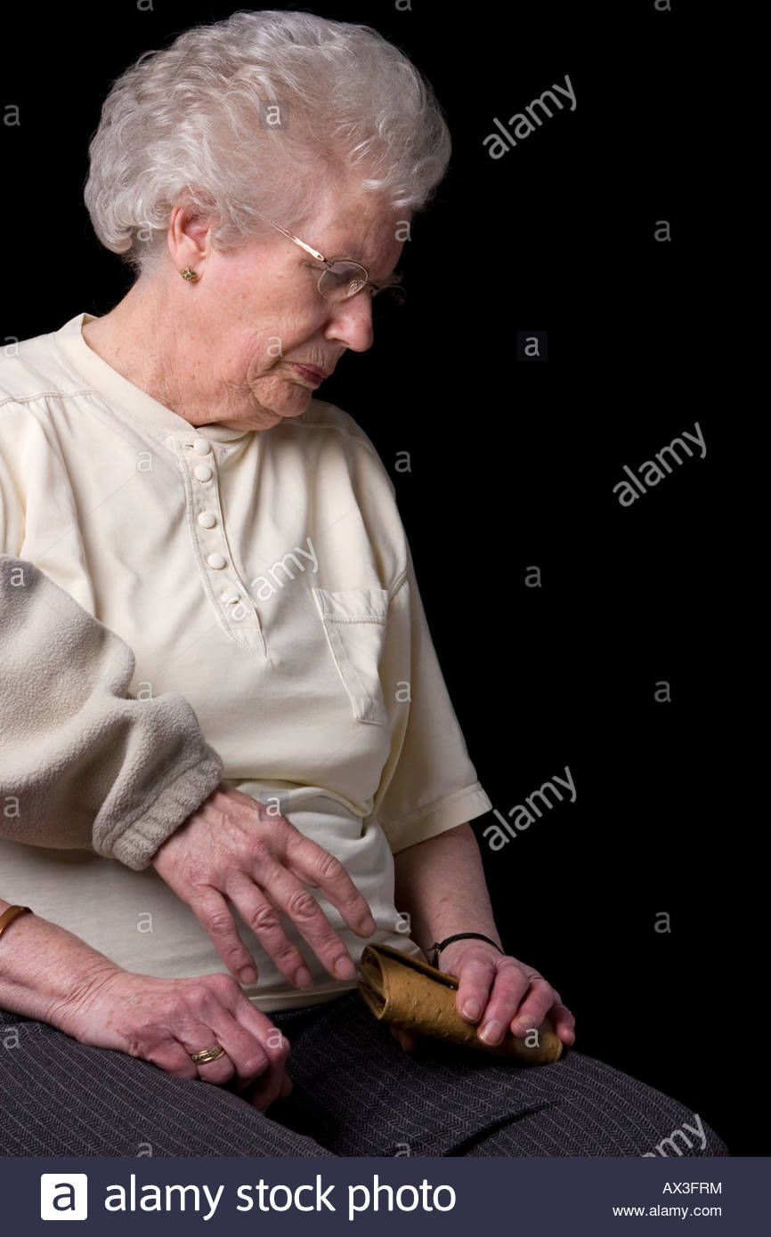 A purse being stolen from an elderly woman. - Stock Image