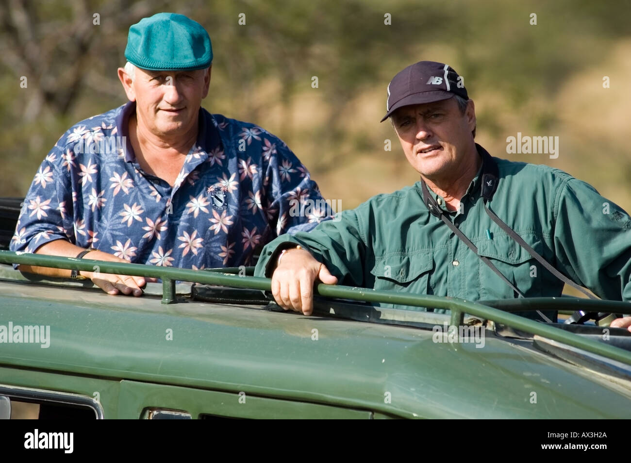 Safari buddies on a game drive while on vacation in Lobo, Serengetti plain, Tanzania, East Africa. - Stock Image