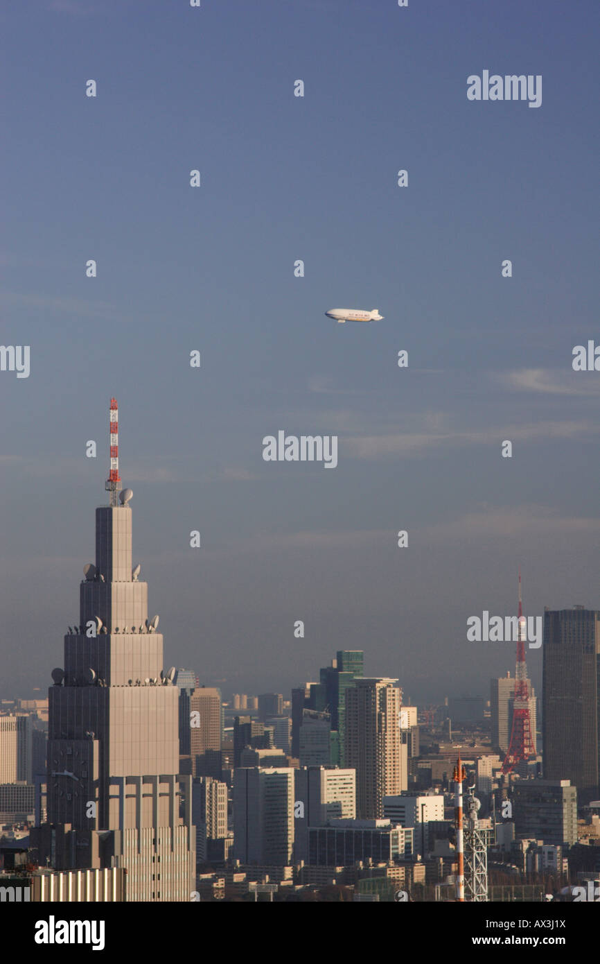 A Zeppelin dirigible belonging to Nippon Airships flying over the skyscrapers of downtown Tokyo, including Tokyo Stock Photo
