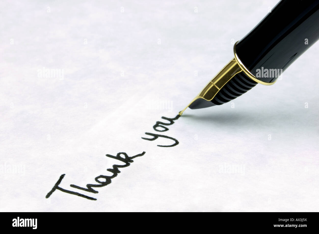 Thank You written on watermarked textured paper using a gold nibbed fountain pen Focal point is on the text - Stock Image