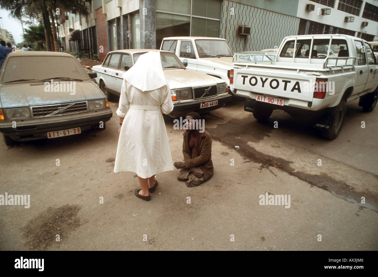 A landmine victim begs for money from a passing nun in the captial of Angola, Luanda. - Stock Image