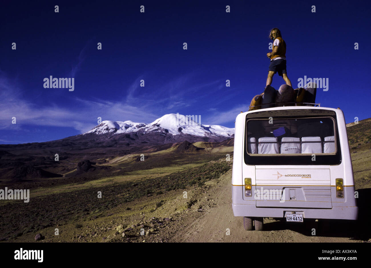 Kayaker looking out over Peru's Altiplano from the top of a bus, with snow-capped mountains in the background - Stock Image